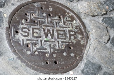 A very old sewer manhole cover set in cobblestone