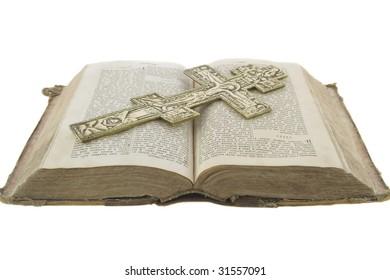 Very old vintage open bible and big church cross on it isolated over white background