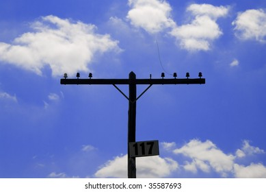 Very old vintage telephone pole with crossbeam and insulators.