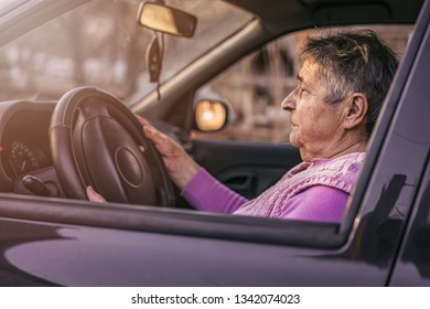 Very old woman driving car. Active senior woman - smiling retired lady driving car. Confident senior woman driving a car.