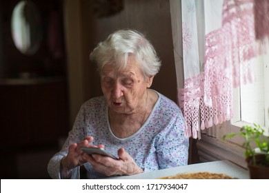 Very old woman use a smartphone in home.