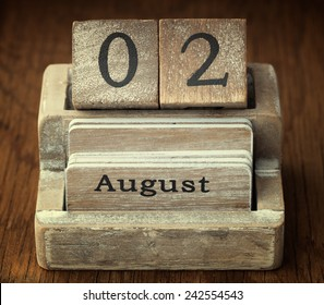 A very old wooden vintage calendar showing the date 2nd August on wood background