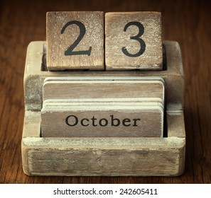 A very old wooden vintage calendar showing the date of 23rd October on wood background