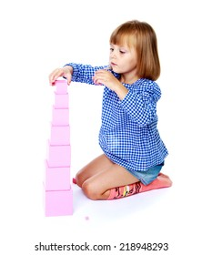 Very passionate little girl collects Montessori pyramid.Education concept happy child.