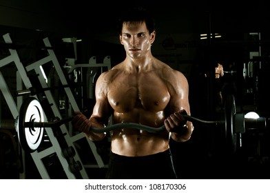 very power athletic guy ,  execute exercise with  weight, in  dark sport-hall