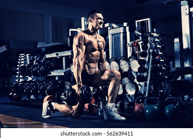 very power athletic guy ,  execute exercise with  dumbbells, in gym, blue; violet tone
