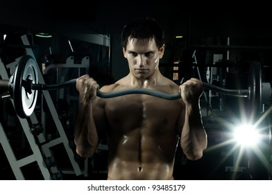very power athletic guy ,  execute exercise with  weight, in  sport-hall, beauty glamour light