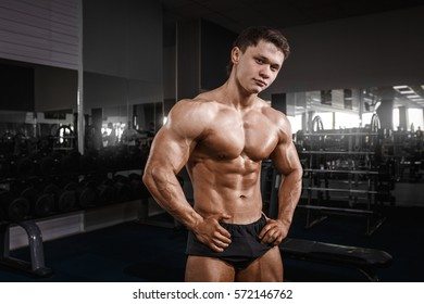 Very power athletic guy standing workout in the gym