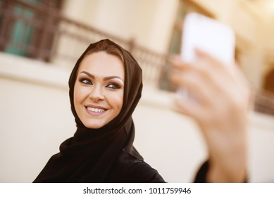 Very pretty girl with green eyes in black hijab taking an amazing selfie with her phone.