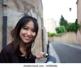 Very pretty young asian woman on bike smiling while on her back home from work on a city street