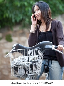 Very pretty young asian woman on bike smiling while calling on her cell phone