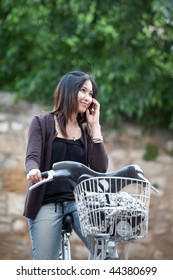Very pretty young asian woman on bike smiling calling on her cell phone, smiling