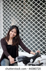 Very pretty young asian woman on bike smiling while commuting/biking to work