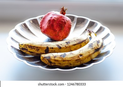 very ripe fruit. Two bananas and pomegranates on a silver metal tray
