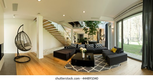 Very roomy ground floor of a contemporary designer house, with a large black lounge and a hanging chair