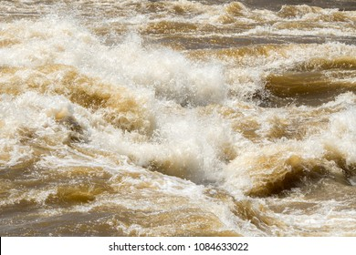 Very rough water in a large river. The water splashes and sprays and is golden in color. Closeup view.