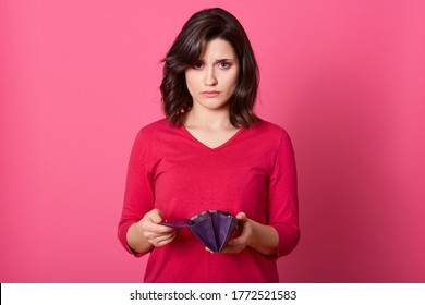 Very sad adult girl with empty purse looking directly at camera, no money left after shopping, has financial problems, has no cash female being in bad mood.
