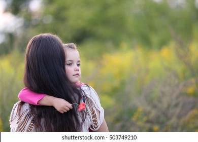very sad little girl in her mother's arms outside, shallow depth of field, room for text