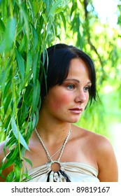 Very sad young girl is standing in leaves of weeping willow in central park at summer day in Riga, Latvia