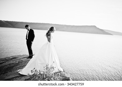 Very sensual and gorgeous wedding couple on the picturesque landscapes on sunset