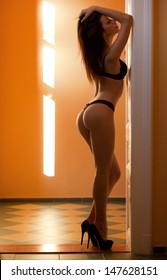 Very sensual slender young brunette model in black lingerie.