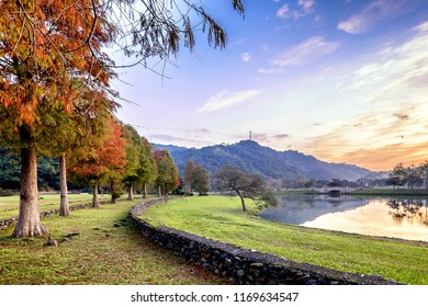 A very serene landscape in Taiwan. It was early morning and the sun rises. The water reflects the beautiful sky colors and trees. The trees are red because of the fall season. The red leaves are rich.