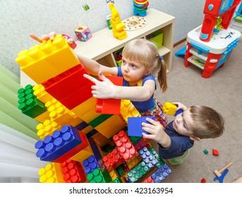 Very serious little boy and girl build big block tower in kindergarten