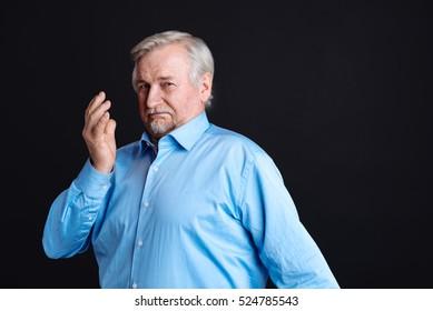 Very serious pensioner looking at camera
