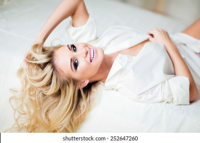 very sexy blonde girl in white shirt smiling , lying on the bed on white sheet