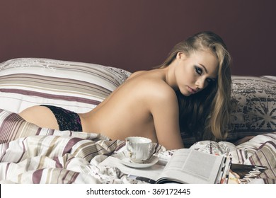 very sexy blonde woman with stylish make-up and freckles, nude back and lace panties is laying on comfortable bed with a vintage cup of tea or cofee and open magazine. She is looking in camera