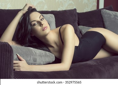 very sexy brunette female with perfect slim body and black lingerie, in sensual pose on velvet sofa