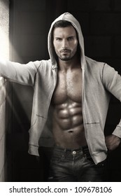 Very sexy male model with open jacket revealing muscular body and nice abs and chest