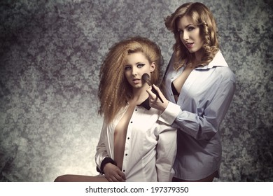 very sexy models posing with open shirt, naked legs and creative hair-style applying bush with brush and looking in camera with sensual eyes. Erotic fashion shoot