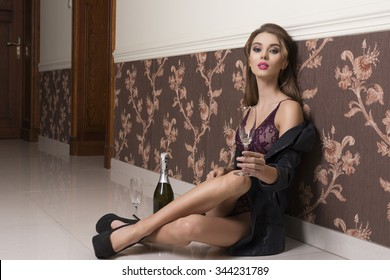 very sexy woman with open jacket, heels and sexy lingerie sitting indoor on floor with champagne and glasses for toast. Erotic new year party