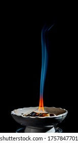 Very simple single blue white smoke trail rising vertically from burning incense in a white ceramic holder. The base of the frankincense flame is vibrant yellow orange against the black background.
