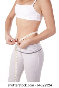 A very skinny woman is measuring her waist.