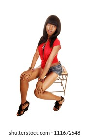 A very slim young black woman sitting in a red blouse and jeans shorts on a small bench with her long black hair for white background.