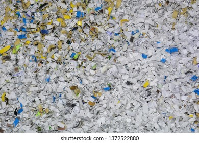 very small bits of documents in the shredder, data protection and security of information theme with confidential documents destroyed in a shredder closeup