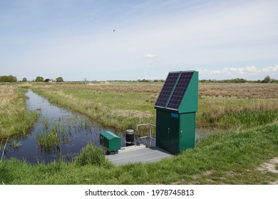 Very small Dutch weir (Dutch: valve weir) with solar panels near a ditch. The weir regulates the water drainage capacity of the surface water body. Spring, meadows, May. Netherlands                    - Shutterstock ID 1978745813