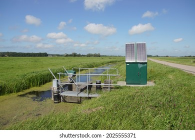 Very small Dutch weir (Dutch: valve weir) with solar panels near a ditch. The weir regulates the water drainage capacity of the surface water body. Summer, meadows, August. Netherlands - Shutterstock ID 2025555371