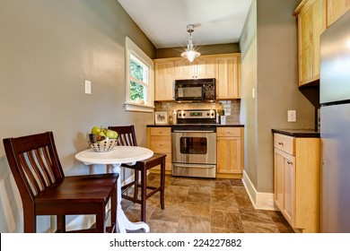 Very small kitchen room with maple storage cabinet, steel stove. Room has white table and two chairs