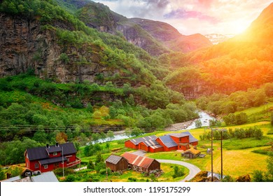 Very small village on the shore of a river in Norway at sunset
