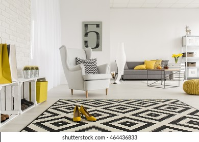 Very spacious living room in white, with yellow decorations and high-heeled shoes in the middle of a modern carpet