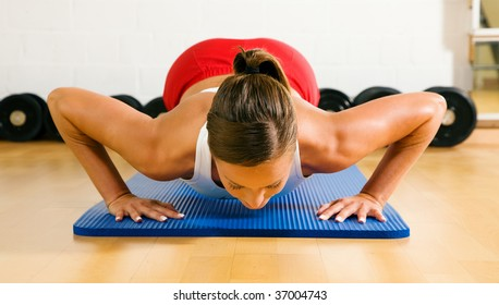 Very sportive woman doing pushups in a gym