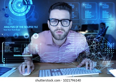 Very strange. Smart young programmer having a difficult day at work while sitting in front of a transparent screen with his hand on a keyboard and looking at the information about cyber attacks