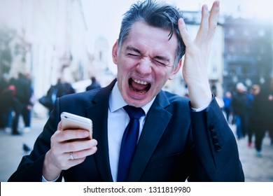 Very stressed and nervous businessman swearing into his mobile phone. The bad news, fail  and negative emotions concept.