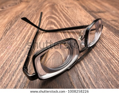 bdf8f3bc4e Very strong eyeglasses with thick minus lenses for myopia and bad eyesight  on a brown wooden