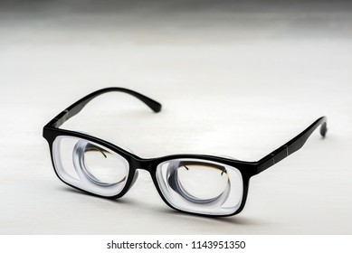 Very strong glasses with thick lenticular lenses in plastic frame for high myopia and poor eyesight for visually impaired people on white painted wooden desk