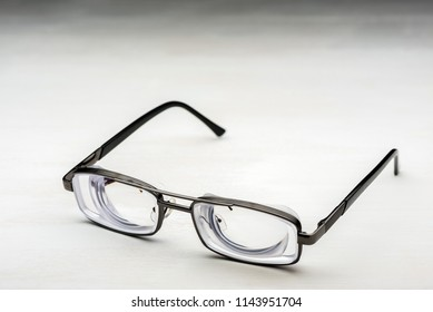 Very strong glasses with thick lenticular lenses in metal frame for high myopia and poor eyesight for visually impaired people on white painted wooden desk
