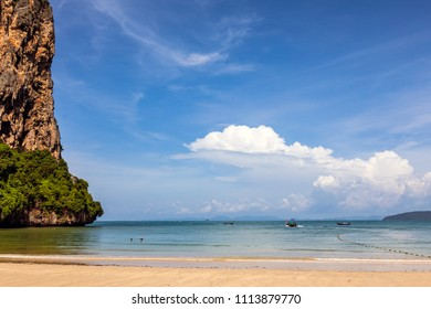 A very sunny day in Krabi beach with mountain and blue sky and patchy clouds visible.